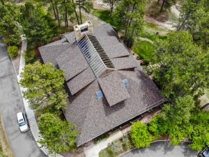 Areial View of a Gray Roof House Surrounded by Trees